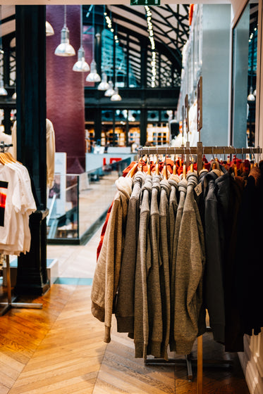 the inside of a store with grey sweaters stacked