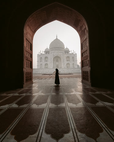 the silhouette of a person standing in a carved archway