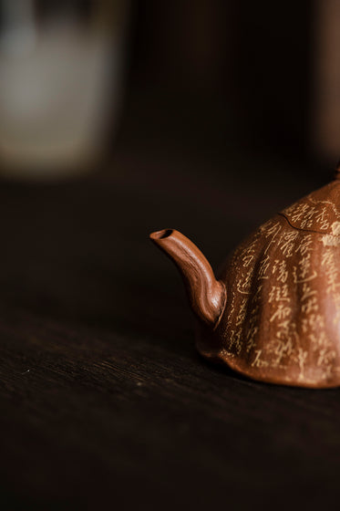 the spout of a rust colored teapot