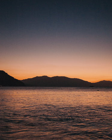 the sun sets behind the silhouette of seaside mountains