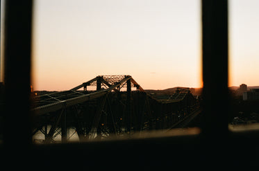 the sun sets on the steel trusses of a bridge