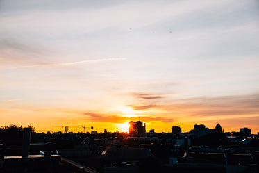 the sun setting over a silhouetted cityscape