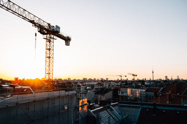 the sunsets over a city rooftops and tall cranes