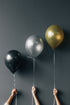 three balloons held against wall