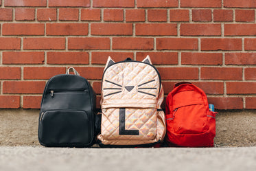 three children's backpacks along brick wall