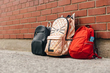 three children's backpacks and a brick wall