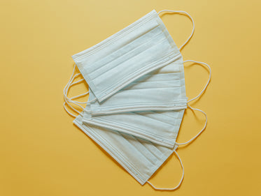 three disposable face masks on a yellow background