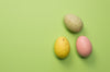 three easter eggs on green background
