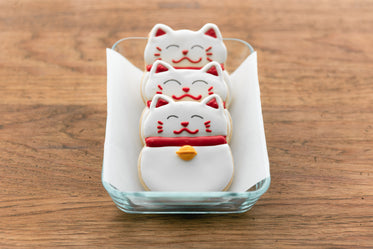 three fortune cat cookies lined in a container