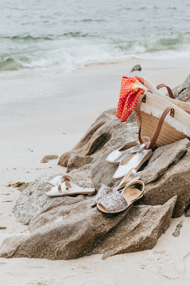 three pairs of summer shoes and a beach bag on the beach
