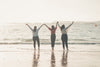 three people hold hands with their arms to the sky