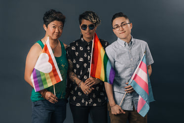 three people holding pride flags