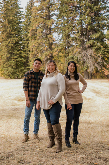 three people in sweaters pose for the camera