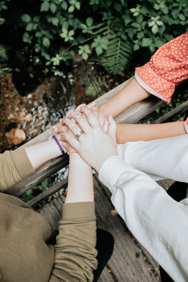 three people pile their hands up on a wooden railing