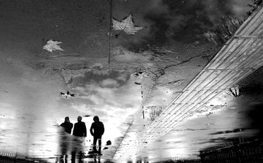 three people reflected in a puddle in black and white