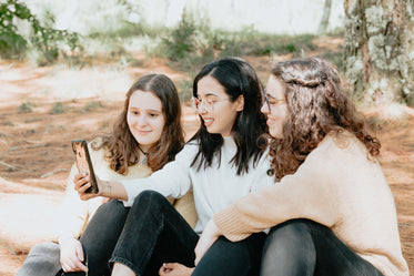 three people sit together outdoors and look at a cellphone