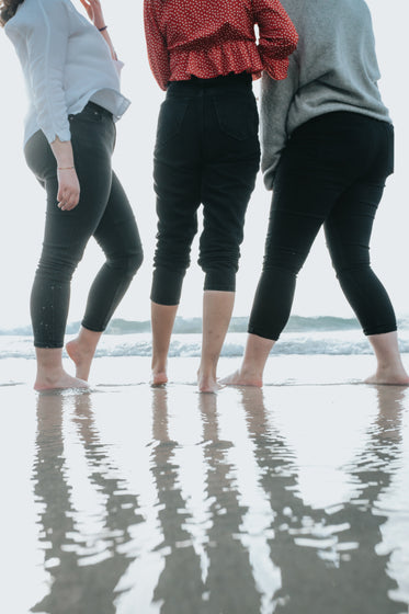 three peoples legs standing on a wet beach