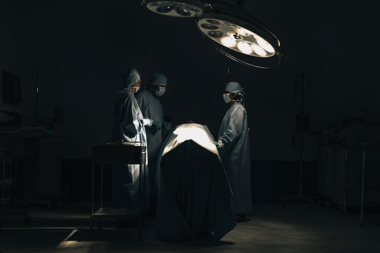 Three Surgeons Stand Around A Patient