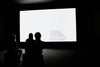 three woman watch a glowing white screen in a dark room
