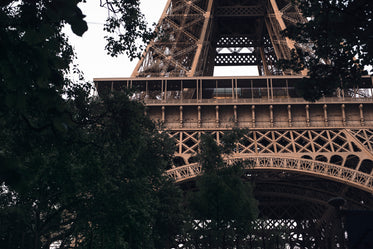 through trees the wrought iron of the eiffel tower
