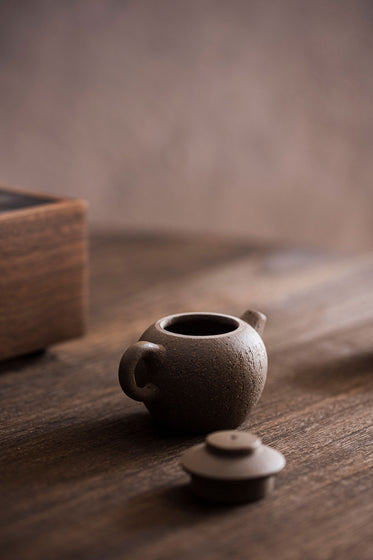 tiny teapot sits with the lid off on a wooden table