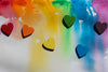 tiny wooden rainbow hearts on watercolour painted background