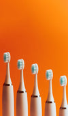 toothbrushes lined up in a row against orange