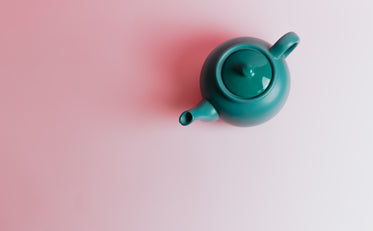 top view of a green teapot on a pink background