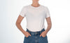 torso of a person standing in white shirt and blue jeans