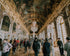 tourists wander through versailles hallways