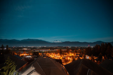 town looks out to snow capped mountains and a starry sky
