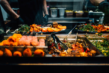 trays of colorful food with tongs
