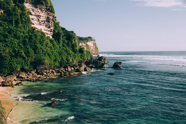 Turquoise Blue Ocean Waters Along Jungle Covered Cliffside