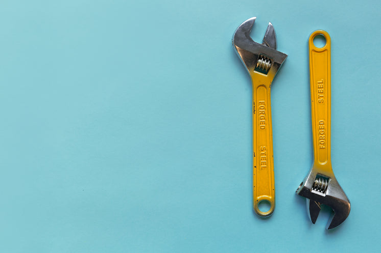 Two Adjustable Wrenches On A Blue Background