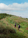 two backpackers taking the path on a green hill