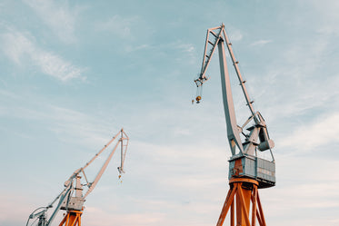 two cranes against a blue sky