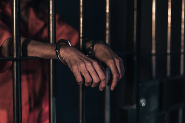 two hands in handcuffs lean on bars of a prison cell