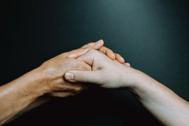 two hands reach to hold a single hand