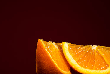 two juicy orange slices against red background