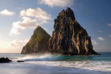 two large mountains rocks sit in a wavy ocean