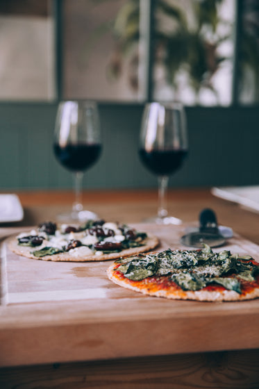 two large pizzas on wooden board with glasses of wine nearby