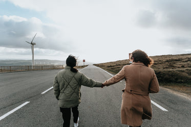 two people hold hands and walk down a paved road