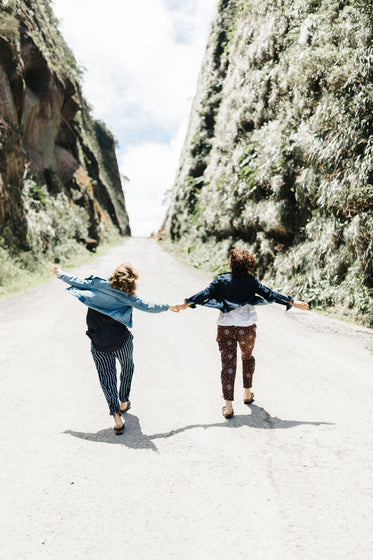 two people holds hands as they walk up a road