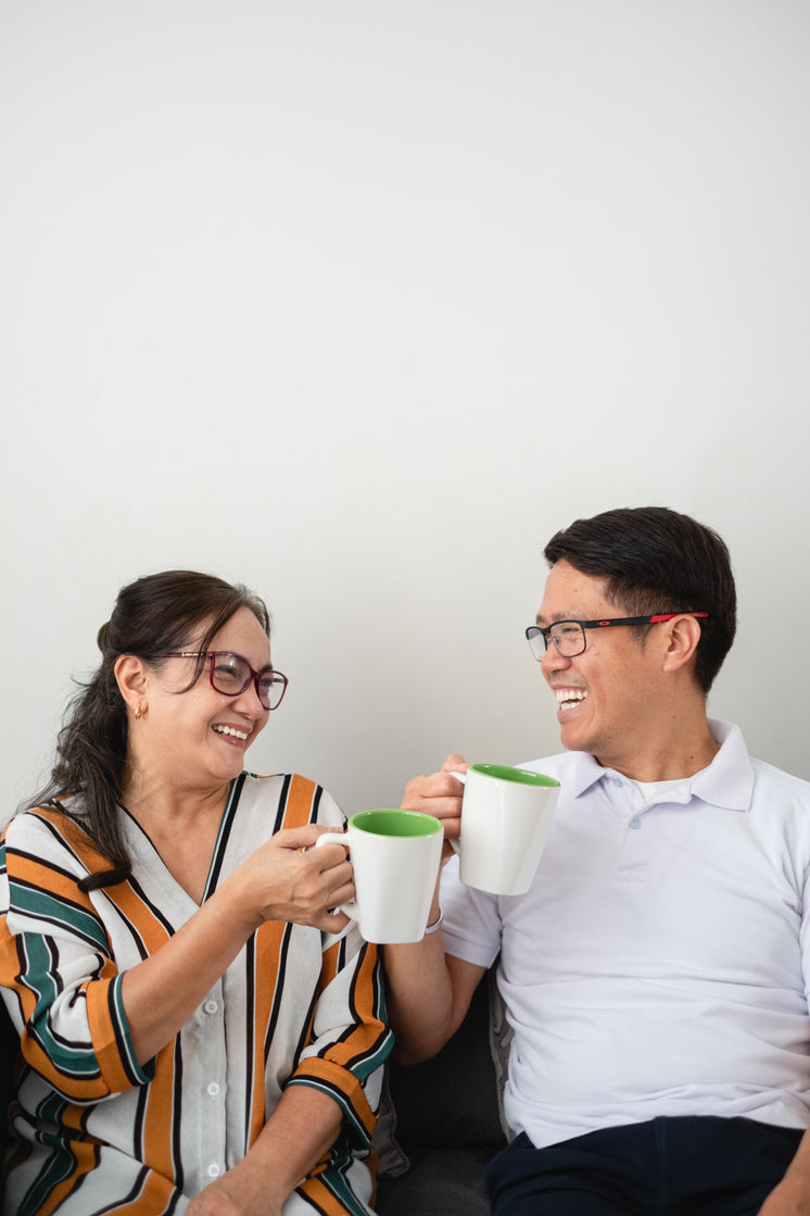 Two People Laugh As They Look Towards Each Other