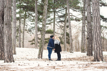 two people on a winter walk look lovingly at each other