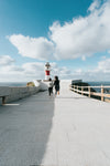 two people run towards a red and white lighthouse