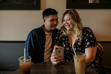 two people share a happy moment in a coffee shop