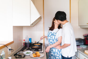 two people share a kiss in the kitchen cooking
