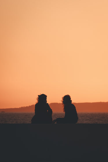 two people silhouetted by the settings sun