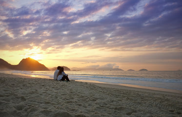 two people sit on the beach and watch the sunset